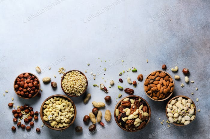 Assortment of nuts in wooden bowls. Cashew, hazelnuts, walnuts, pistachio, pecans, pine nuts, peanut