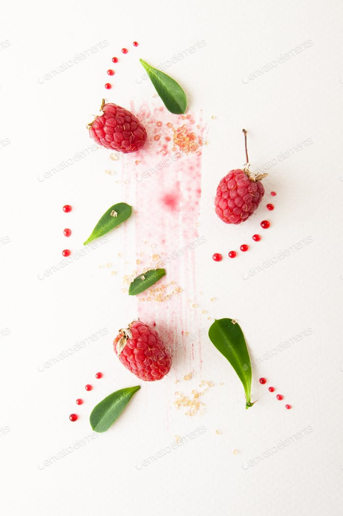 Ripe raspberries, green leaves and jam drops on a white backgrou