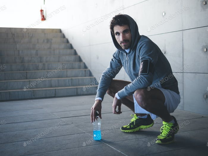 Male athlete having a break after jogging