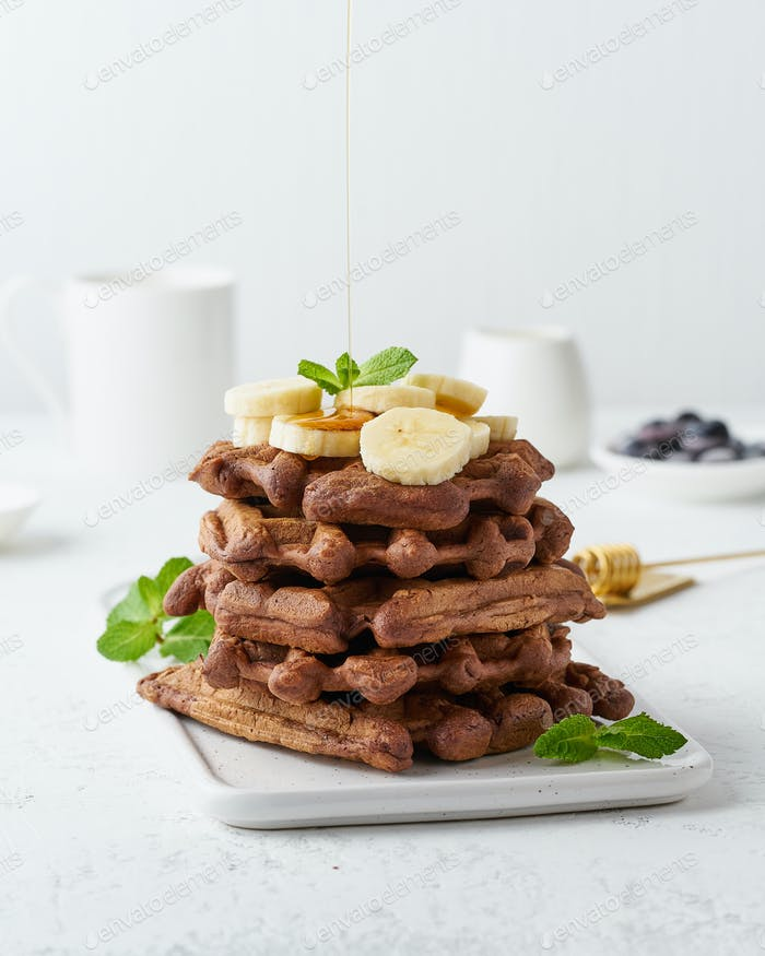 Chocolate banana waffles with maple syrup on white table, side view, vertical. Sweet brunch