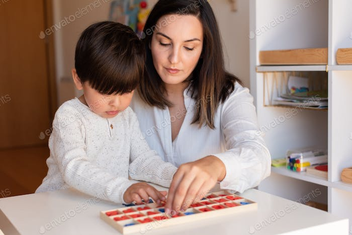 Kid learning to write and read with a alphabet and mother or teacher help.