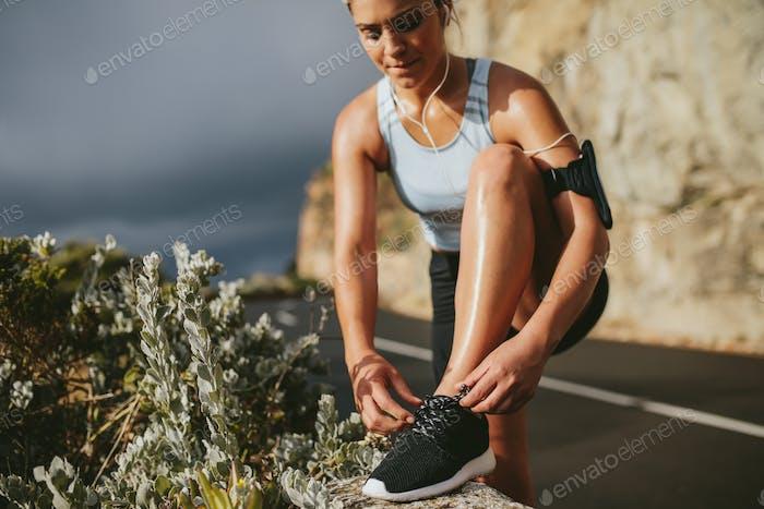 Weibliche Läufer binden Schnürsenkel