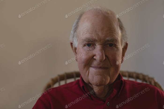 Front view of happy senior man sitting and looking at camera in nursing home