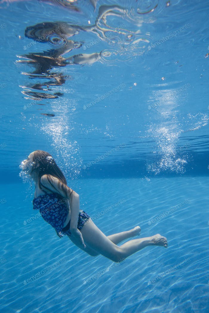 A child swimming under water in a swimming pool.