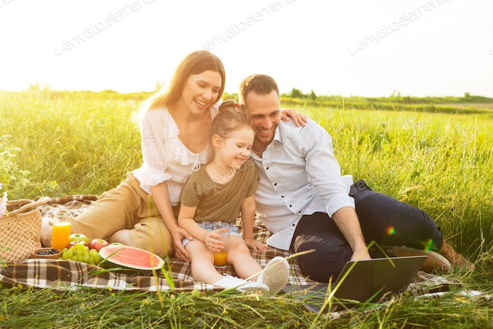 Happy family together on a picnic with personal computer