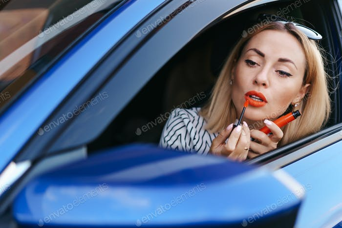 Woman looking in cars side mirror and putting on lipstick