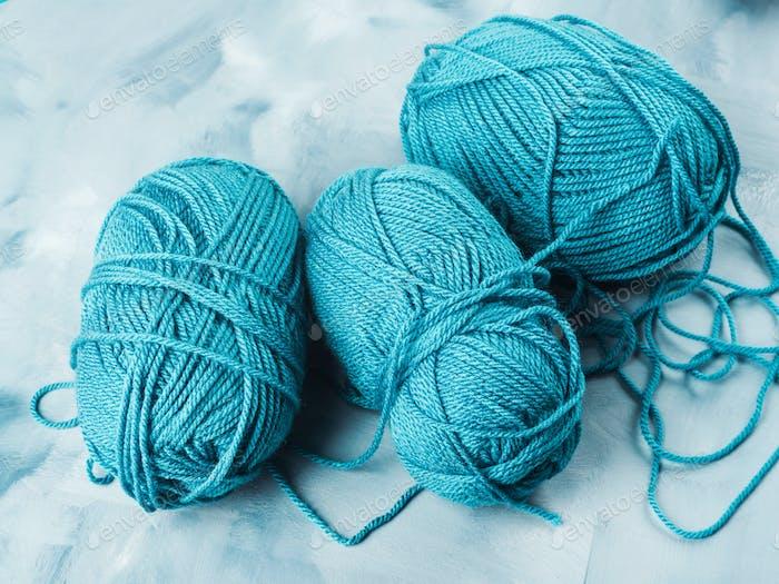 Blue wool knitting yarn balls on faded background