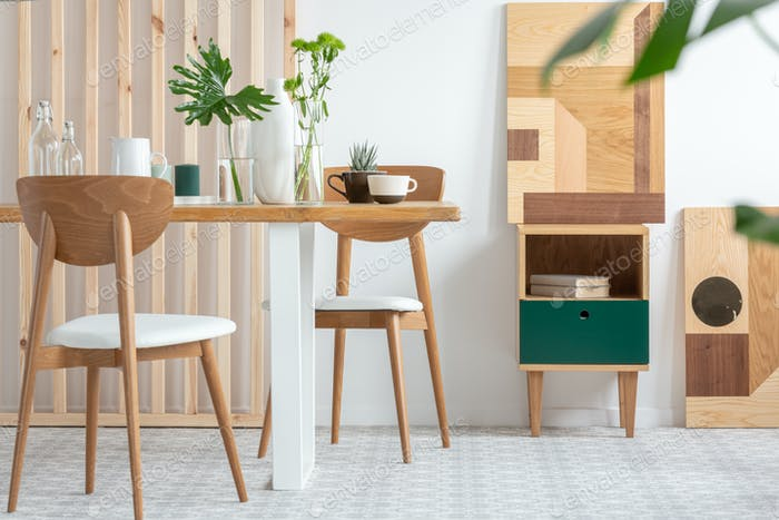 Green leafs in vases on long wooden table in trendy white dining room