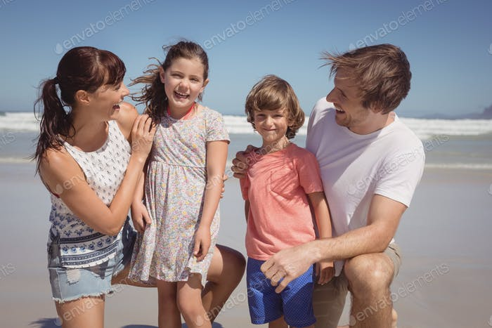 Happy siblings with parents at beach