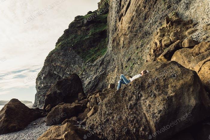 young man lying on cliff and enjoying majestic icelandic landscape