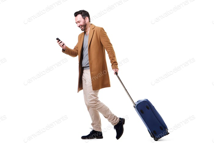 Full body happy man walking with mobile phone and suitcase against isolated white background