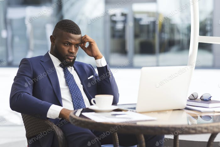 Businessman At Laptop Reading News About Crisis Sitting In Cafe