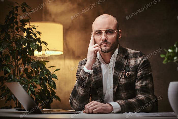 Bald serious thinking european well-dressed businessman sitting in the office