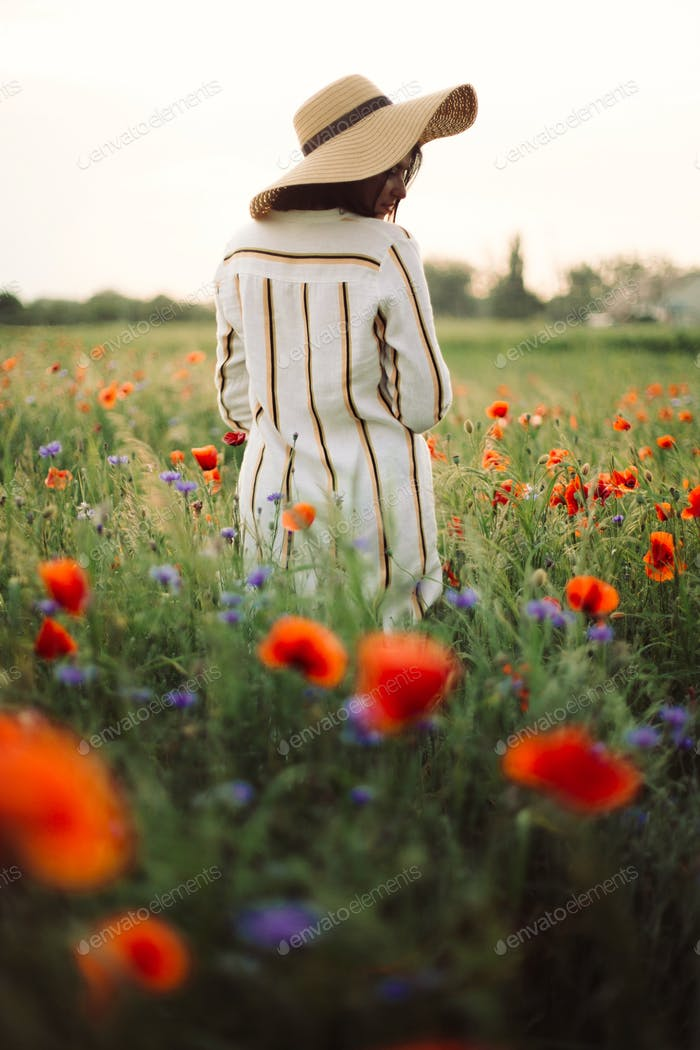 Stylish woman in rustic  dress and hat walking in summer meadow among poppy and wildflowers