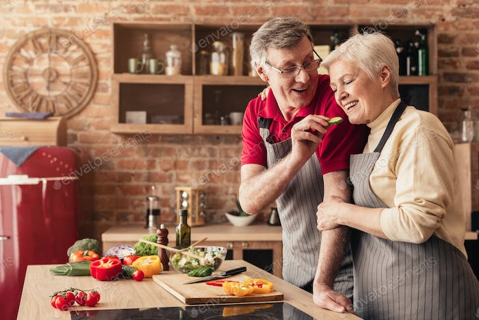 Loving aged man feeding his wife with cucumber in kitchen