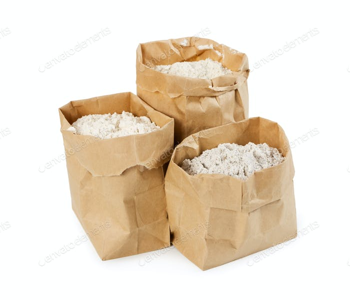 Flour and flour mixture in paper bags isolated on white