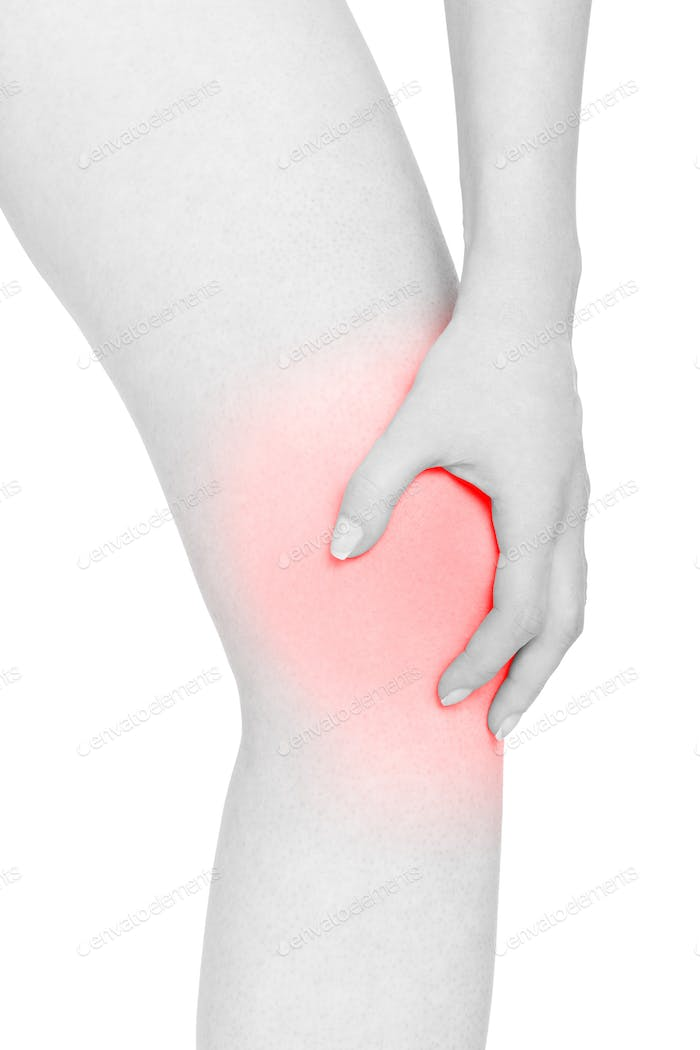 Young woman holds her hand on knee, red pain area isolated on wh