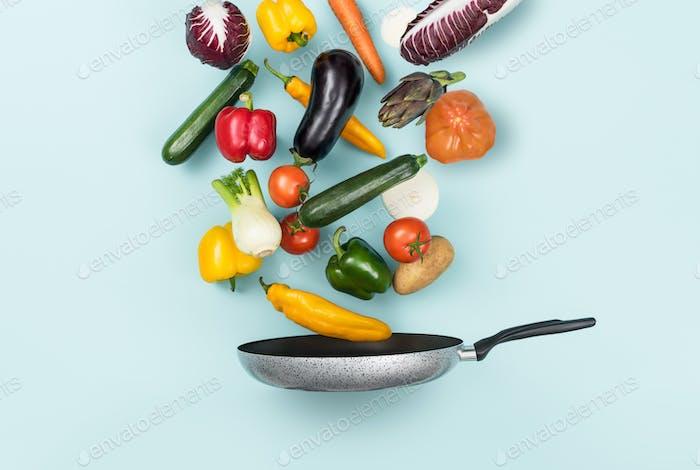 Frisches, gesundes Gemüse, das in einer Pfanne fällt