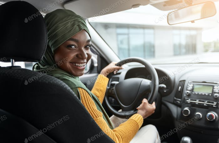 Buying Automobile. Smiling Black Muslim Lady In Hijab Testing New Car