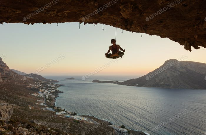 Young female rock climber hanging on rope in asana position