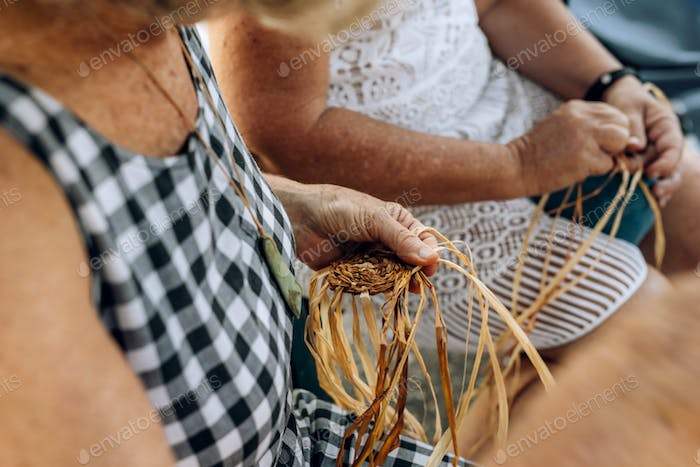 Two old females weaving baskets on the craft workshop. Hands holding the craftwork, close up shot