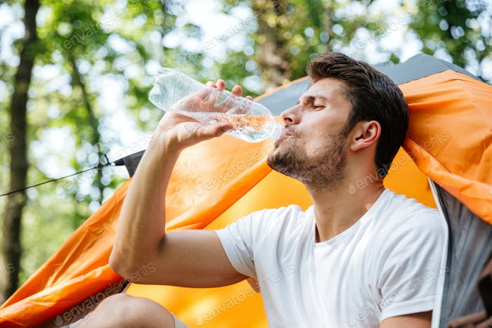 Attractive man tourist sitting and drinking water in touristic tent