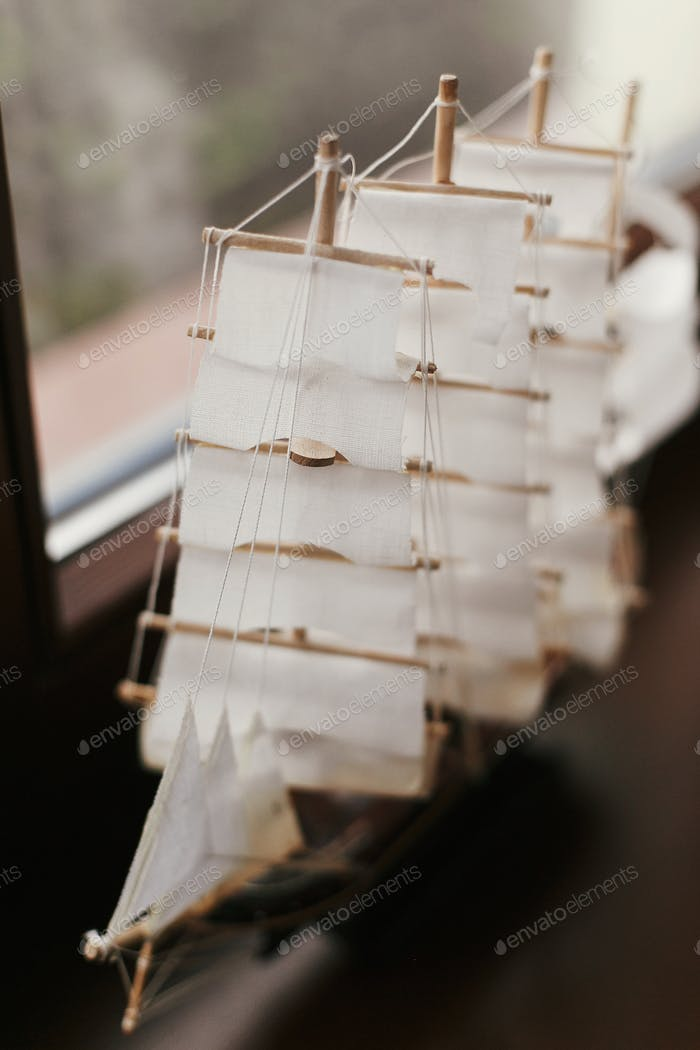 Wooden boat to with sails at window