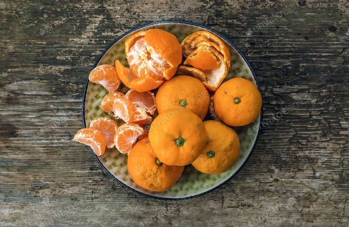 Plate of fresh ripe juicy mandarins over a rough wood background