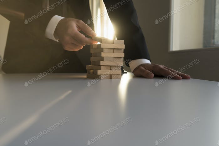 Businessman building a tower of wooden blocks