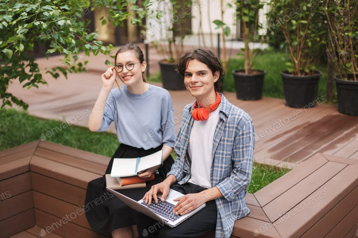 Couple of smiling students sitting on bench with books and laptop and happily looking in camera