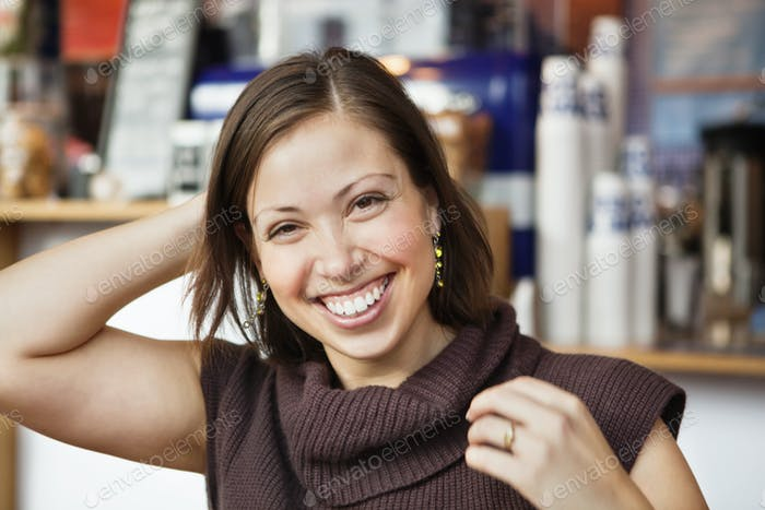 Portrait of happy young woman with hand behind head at cafe