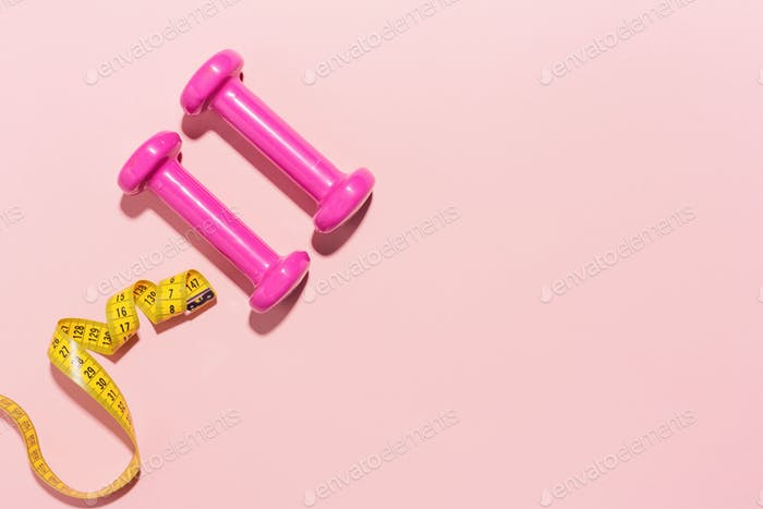 Dumbbells flat lay on pink background