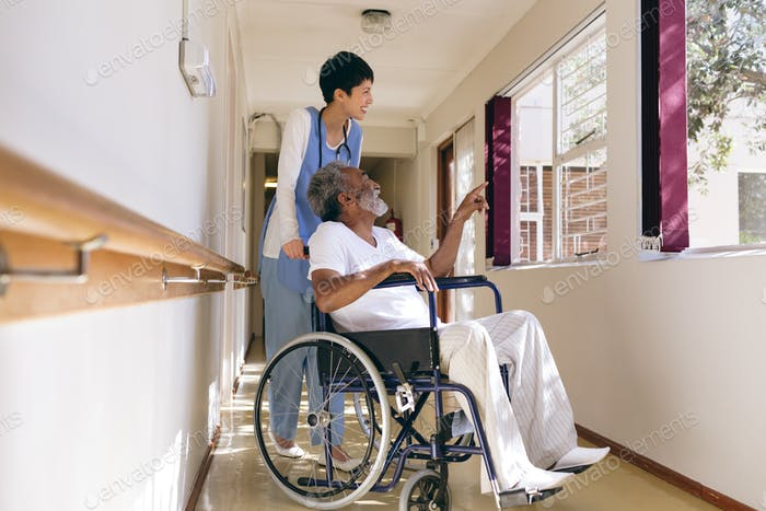 Female nurse and senior male patient interacting with each other at retirement home