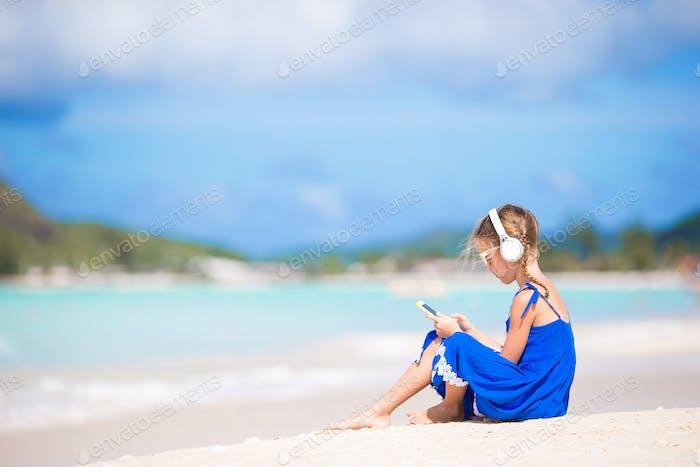 Kleines Mädchen hören die Musik durch Kopfhörer am Strand