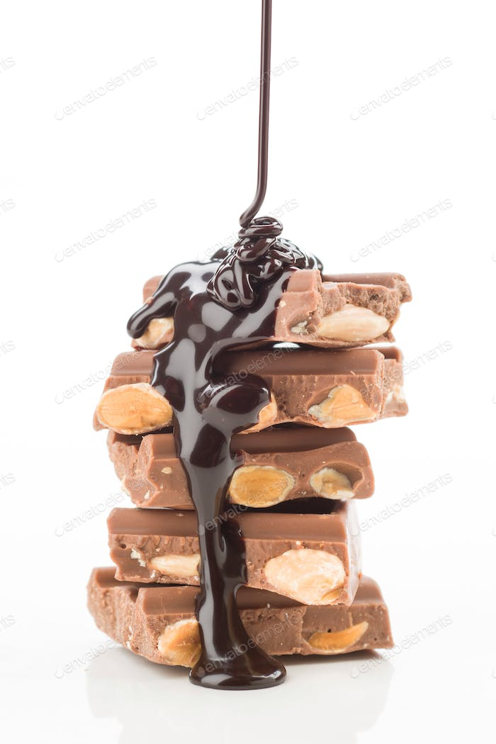 thread of liquid chocolate, falling tower of pieces of chocolate on white background