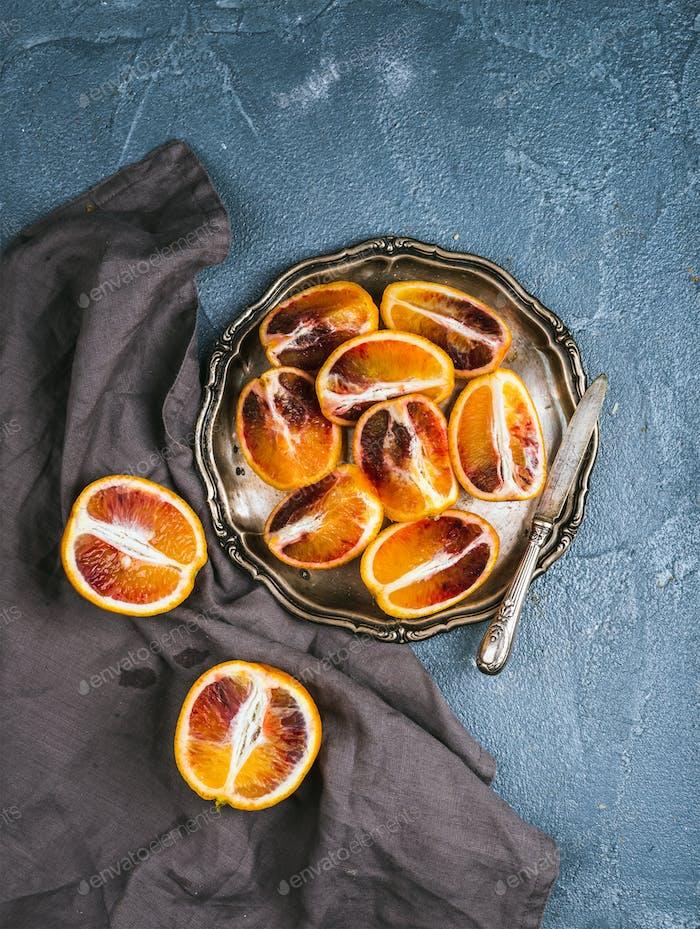 Blutige rote sizilianische Orangen in Viertel in Vintage-Metallplatte geschnitten