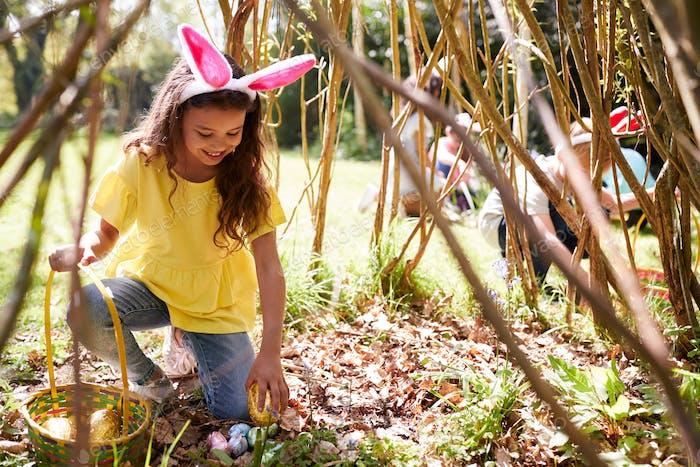 Group Of Children Wearing Bunny Ears Finding Easter Eggs Hidden In Garden