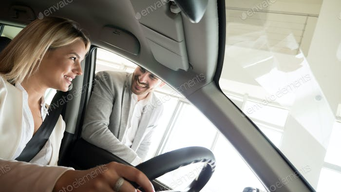 Autogeschäft, Autoverkauf, Konsum- und Menschenkonzept - glückliche Frau mit Autohändler in Auto