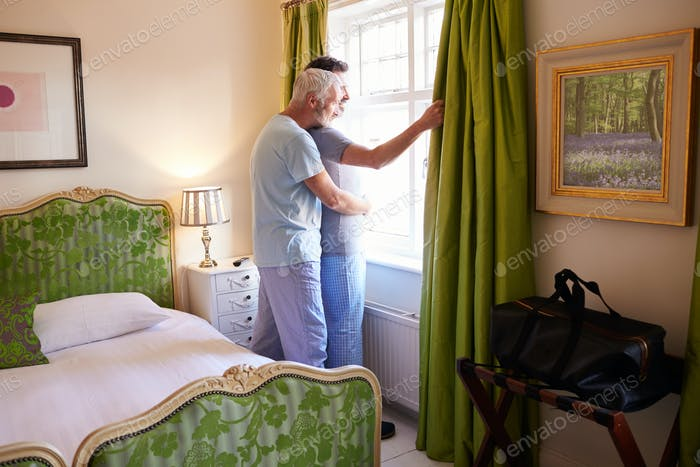 Männlich Paar Umarmung Blick aus Hotel Zimmer Fenster, volle Länge