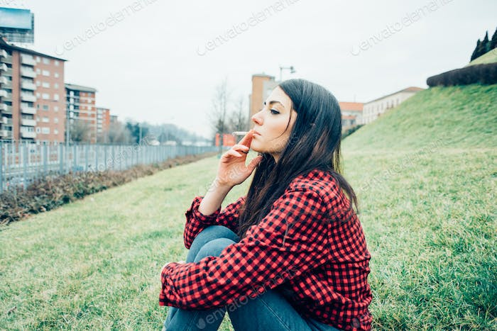 Young beautiful caucasian woman sitting in a park outdoor in the