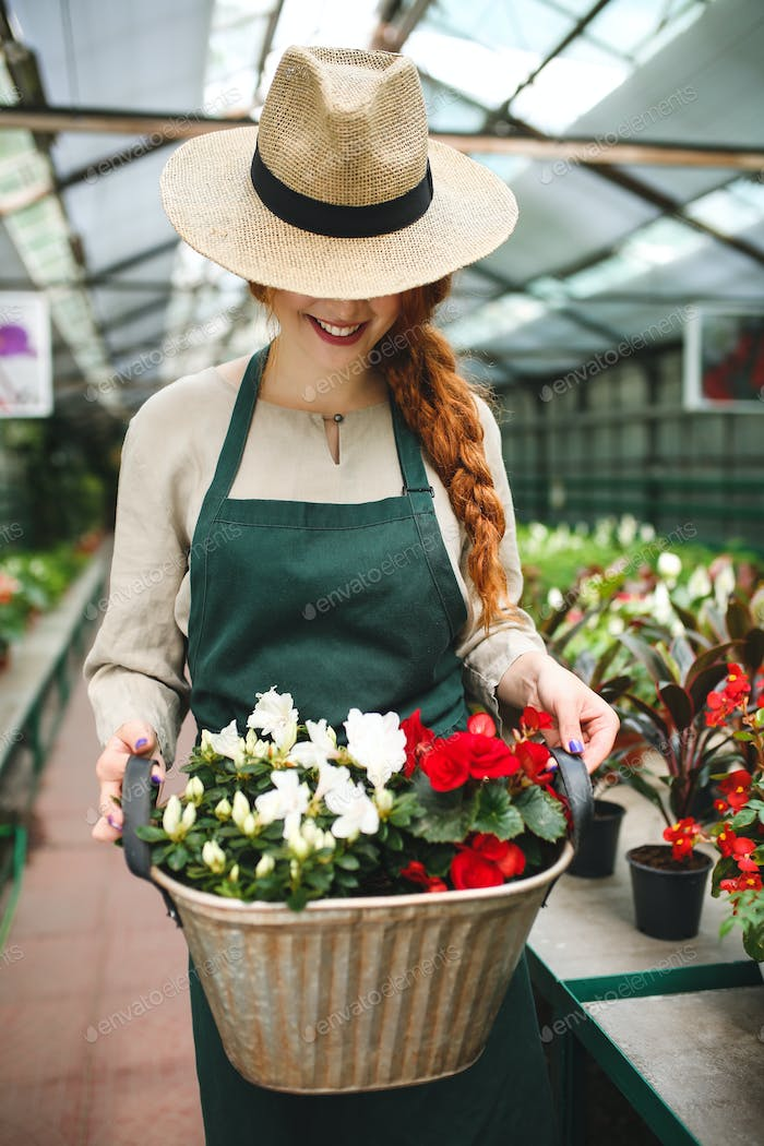 Smiling florist in apron and hat standing and holding flowers in metal basket working in greenhouse