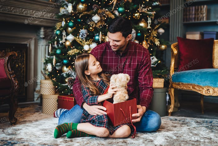 Girl holds teddy bear, receives unexpected gift from affectionate father, being thankful to him