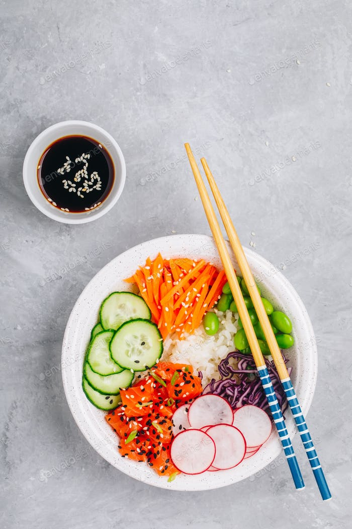 Salmon poke bowl with rice, radish,cucumber, carrots, edamame, red cabbage and sesame seeds.