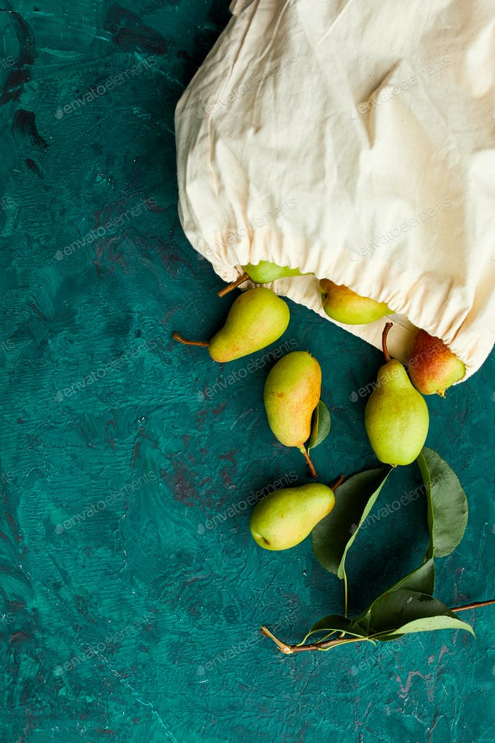 Fresh ripe fruits pears in string reusable shopping eco bag.