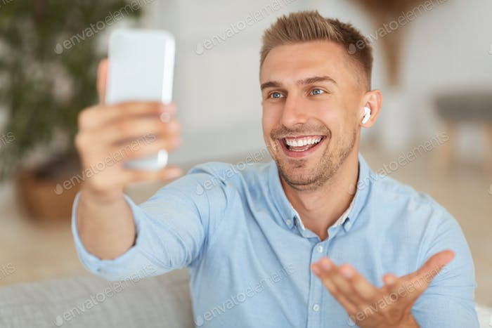 Happy guy using mobile phone for video call