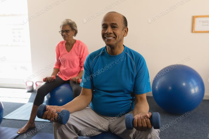 Front view of happy senior man exercising with dumbbells in fitness studio