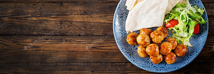 Meatballs in sweet and sour glaze on a plate with pita bread and