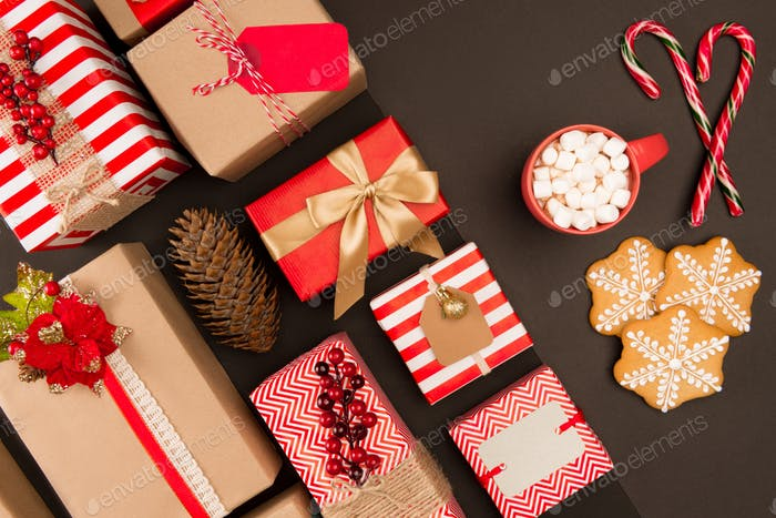 top view of christmas gifts, cookies, candy canes and hot beverage with marshmallows