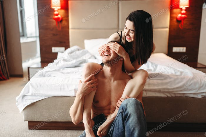 Sexy love couple hugs and have a fun in bedroom