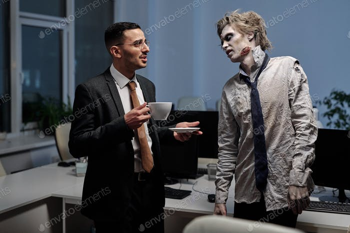 Young elegant businessman talking to male zombie in office